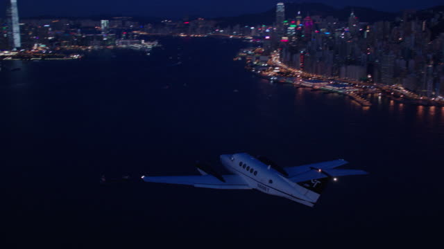 night aerial air to air ms following twin engine beechcraft king air r-l over hong kong harbor and skyline - hong kong stock videos & royalty-free footage