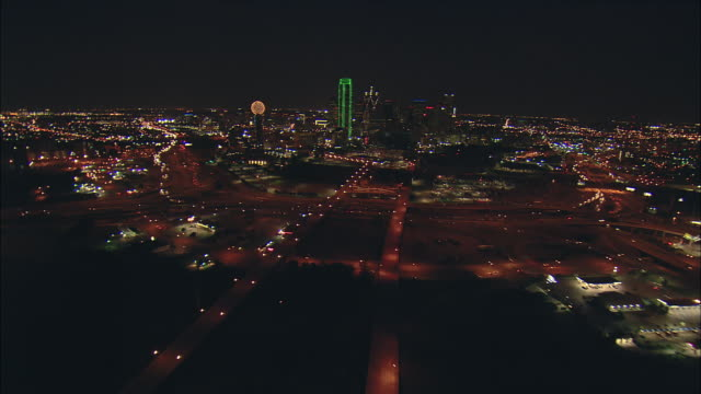 Night aerial low altitude approach over Stemmons Freeway toward downtown Dallas and Reunion Tower