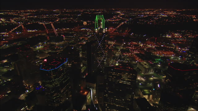 Night aerial low altitude approach past Reunion Tower then low flight along core buildings of downtown Dallas