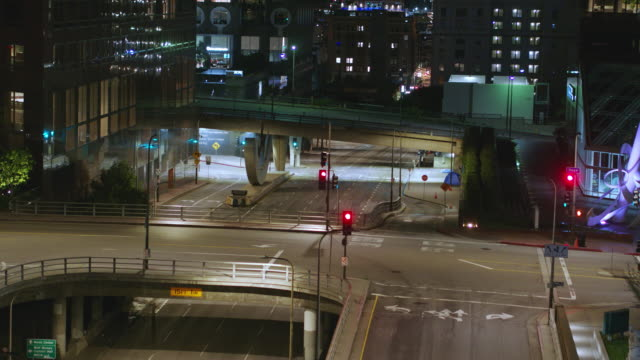 night aerial of empty downtown los angeles street during the covid-19 pandemic - social issues stock videos & royalty-free footage