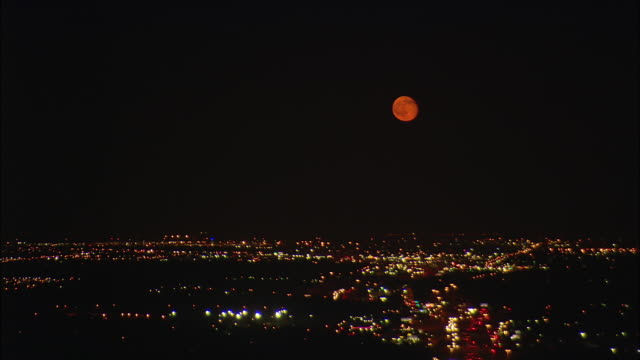 Night aerial shot of full moon low on horizon over suburbs of Dallas