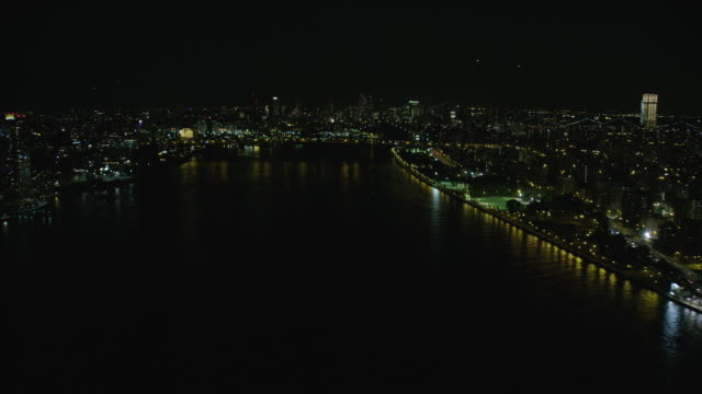 vidéos et rushes de night aerial view of east river in new york city - vue subjective d'un avion