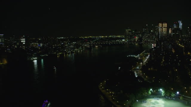 night aerial view of the east river in new york city - east river stock videos & royalty-free footage