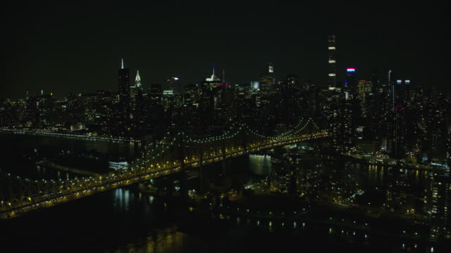 Night Aerial View Of The Queensborough Bridge In New York City Then Revealing Midtown Manhattan