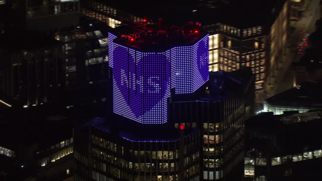night aerial views of tower 42 skyscraper in the city of london lit up blue in support of the nhs and medical workers fighting to keep us safe from... - blue stock videos & royalty-free footage