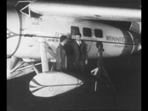 """aviators wiley post and harold gatty stand in front of their airplane, the """"winnie mae,"""" which has the pathe rooster logo on it and the name of their... - circumnavigation stock videos & royalty-free footage"""