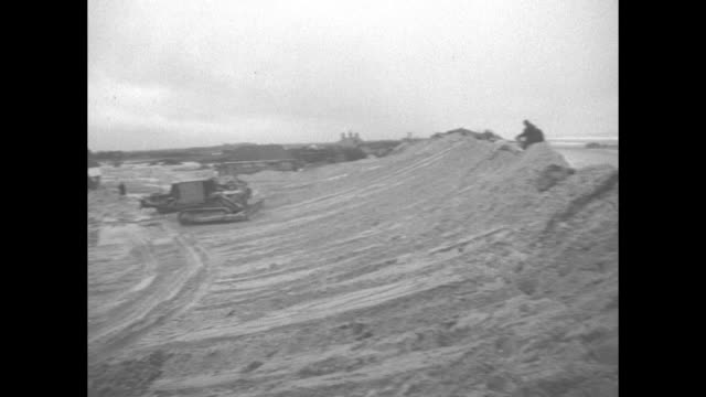 bulldozers push sand into dunes after flooding on Canvey Island England / day same shot see ocean over the dunes / man sorts through rubble of...