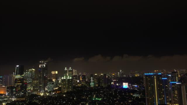 vídeos y material grabado en eventos de stock de night city lights sparkle in the jakarta skyline with a black sky and gray clouds hanging overhead - yakarta