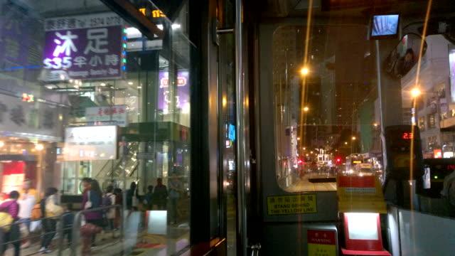 vidéos et rushes de scène de nuit rue de la ville de hong kong à l'intérieur d'un tram - ligne de tramway