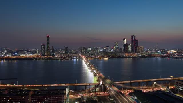 stockvideo's en b-roll-footage met night cityscape of yeouido area with gangbyeon expressway and wonhyodaegyo bridge over han river / seoul, south korea - straatnaambord