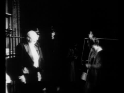 crowd at London event with light in background / UK Prime Minister Winston Churchill stands in doorway of 10 Downing Street with wife Clementine...