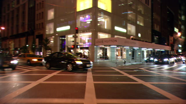 DS Night driving in Midtown Manhattan, with a left turn, taxis, buses, and upscale storefronts / New York City, New York, United States