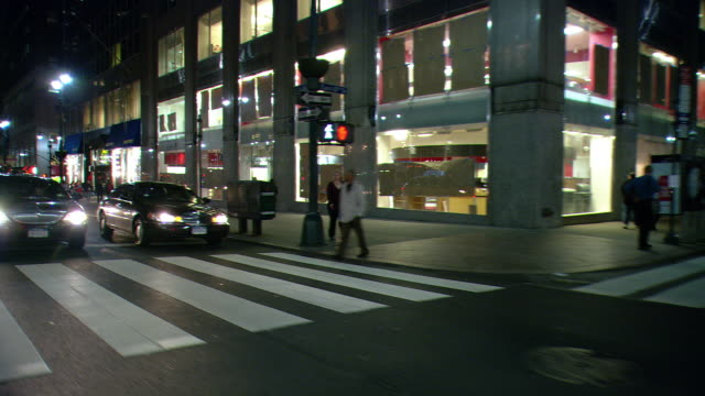 DS Night driving in Midtown Manhattan, with an intersection, pedestrians at a crosswalk, taxis, traffic, and upscale storefronts / New York City, New York, United States
