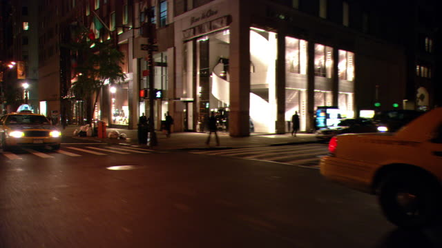 DS Night driving in Midtown Manhattan, with taxis, traffic, and upscale storefronts / New York City, New York, United States