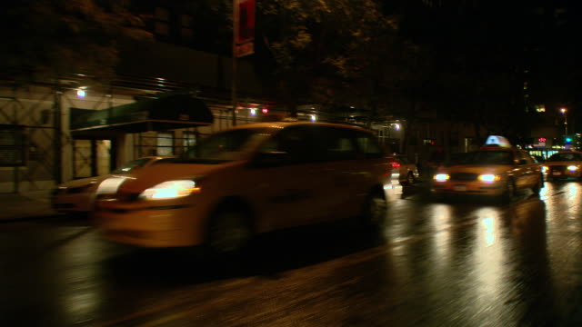 ds night driving in traffic through the upper east side, passing a shopping district in the rain / new york city, new york, united states - bロール点の映像素材/bロール