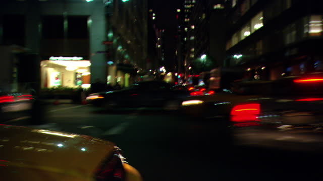 vídeos y material grabado en eventos de stock de ds night driving on park avenue, with upscale storefronts, a parking garage, and traffic backed up at an intersection / new york city, new york, united states - pasear en coche sin destino
