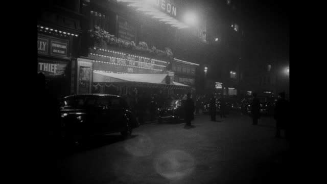 "odeon cinema in london's leicester square; traffic passes in foreground; sign touts royal command performance of ""to catch a thief"" / tree obscures... - film premiere stock videos & royalty-free footage"