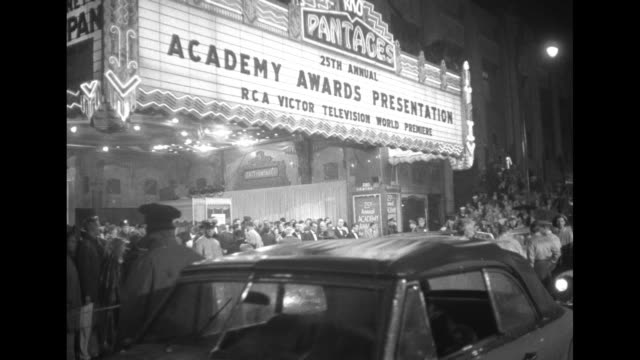 ext pantages theatre with marquee touting the awards ceremony and the fact that this is the first televised academy awards ceremony spectators stand... - oscars stock videos & royalty-free footage