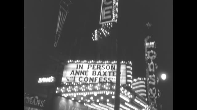 vidéos et rushes de exterior of palace theatre with marquee touting the film premiere of i confess / actress anne baxter walks toward theater with director alfred... - montreal