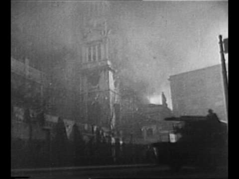 LS fire burns at end of London street during World War II Blitz / helmeted firefighters move about silhouetted by flames in background / flame shoots...