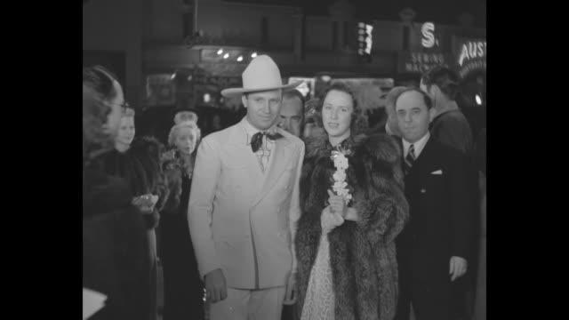 gene autry and his wife, ina mae autry, arrive at the los angeles premiere of 'the hunchback of notre dame'; he wears a western-themed outfit and... - film premiere stock videos & royalty-free footage
