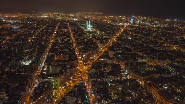 night hyperlapse / motion time lapse of barcelona city sagrada familia skyline. night barcelona cityscape aerial panorama. cityscape with typical urban octagon blocks. catalonia, spain - barcelona spanien stock-videos und b-roll-filmmaterial