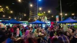 night illuminated kuala lumpur city center street food crowded market panorama 4k timelapse malaysia