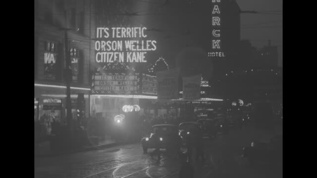 lighted marquees and signs on broadway in times square manhattan with marquee touting orson welles citizen kane at right and traffic moving on street... - film premiere stock videos & royalty-free footage