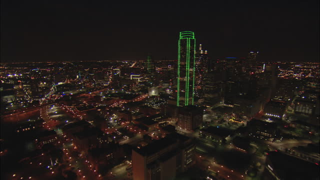 Night low altitude aerial approach to Dallas Hyatt Regency and Reunion Tower then close pass by Bank of America Plaza with full moon near horizon in BG