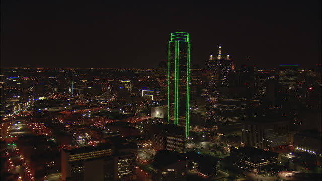 Night low altitude aerial pivoting shot of downtown Dallas skyline with Reunion Tower passing close in foreground
