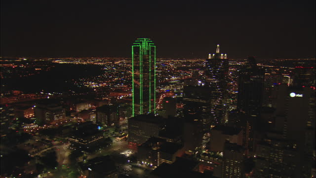 Night low altitude aerial pivoting turn around green-lit Bank of America Plaza and Renaissance Tower in downtown Dallas