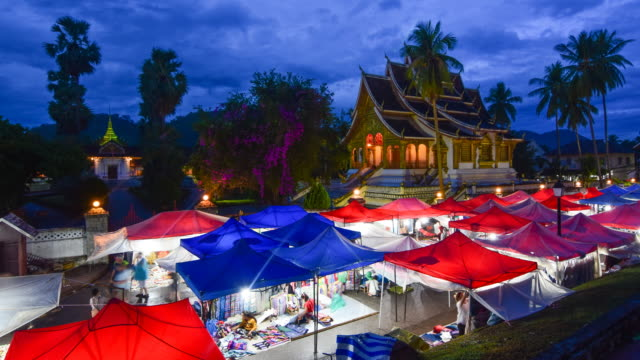 night market around buddhist temple in luang prabang,laos - temple street market stock videos and b-roll footage