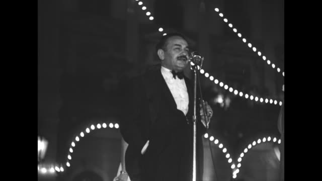 montage actor edward g. robinson speaks at microphone during the cannes film festival's opening party at the grand hotel / party attendees mingle,... - カンヌ映画祭点の映像素材/bロール