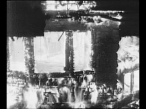 montage buildings burn in aftermath of san francisco earthquake / ls down street with smoke from burning buildings at end / sunken portion of street... - 1906 stock-videos und b-roll-filmmaterial