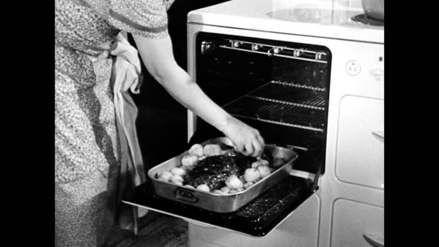 vídeos y material grabado en eventos de stock de night on the farm / father switches off outdoor lights and goes inside / housewife takes roast out of the oven / family smiling and happy as they sit... - 1940