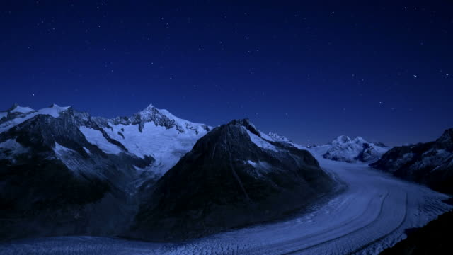 vídeos de stock e filmes b-roll de night over glacier turns into new day, rising moon/rising sun lights scene - suíça