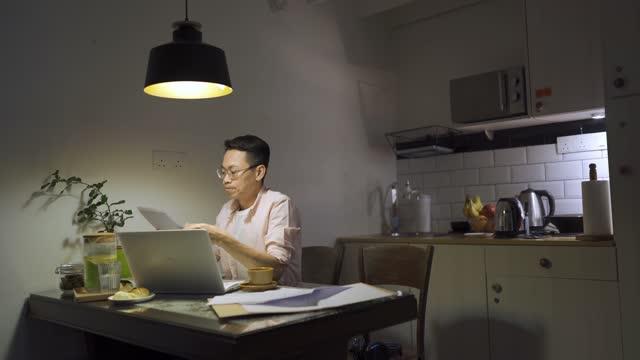 夜間過度勞累亞洲華人男性在家餐廳工作到很晚, 晚上獨自處理財務帳單, 情緒緊張 - 僅一成熟男士 個影片檔及 b 捲影像