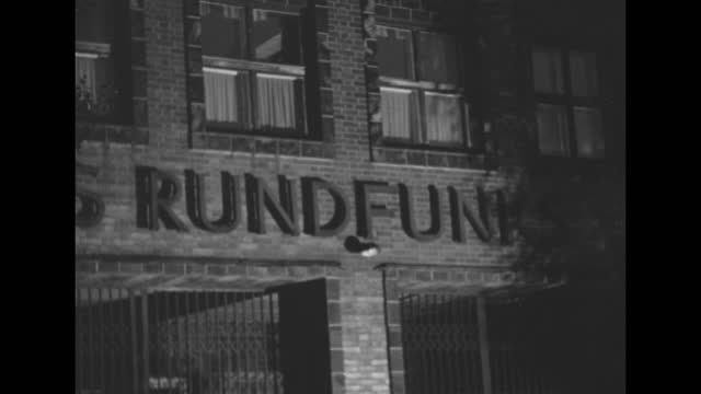 pan to follow western allied military police officer as he walks back and forth in front of berlin broadcasting studio haus des rundfunks, which was... - document stock videos & royalty-free footage