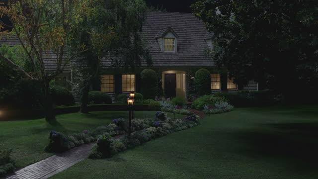 night pan up & establish nice house w/lights on - grounds stock videos & royalty-free footage