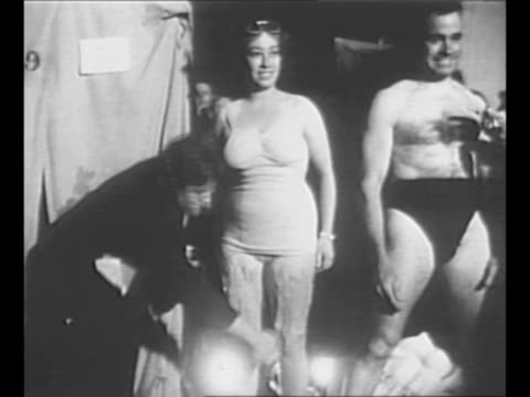 people coat swimmers with grease to help them swim the english channel during a 1950 contest / montage people rub grease on male and female swimmers... - waten stock-videos und b-roll-filmmaterial