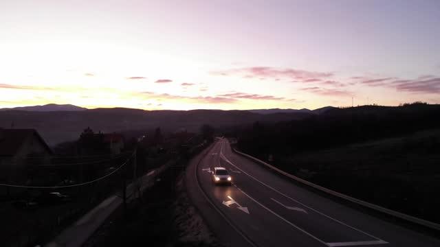 giro notturno. vista aerea. drone girato sopra la strada, tramonto in lontananza - fanale anteriore video stock e b–roll