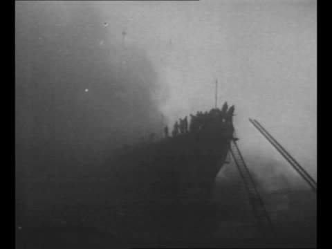 sailors aim hoses at uss lafayette which is on fire in new york harbor pan up to smoky air and people on deck aboard the ship / montage ship burns /... - lying on side stock videos & royalty-free footage