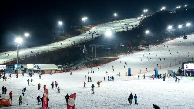 night scenery of large group of people and ski lift at the ski resort - ウィンタースポーツ点の映像素材/bロール