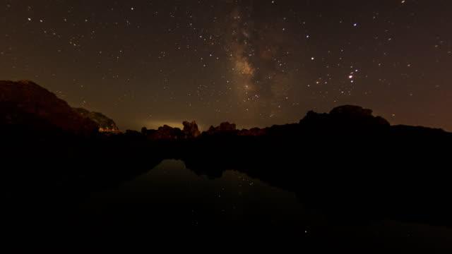 vídeos de stock, filmes e b-roll de night scenery of socheonji(caldera lake) at mountain peak in hallasan national park with milky way - time lapse da noite para o dia