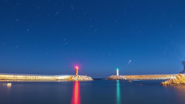 vídeos de stock e filmes b-roll de night scenery of star trail and two lighthouses at the sea - rasto de estrelas