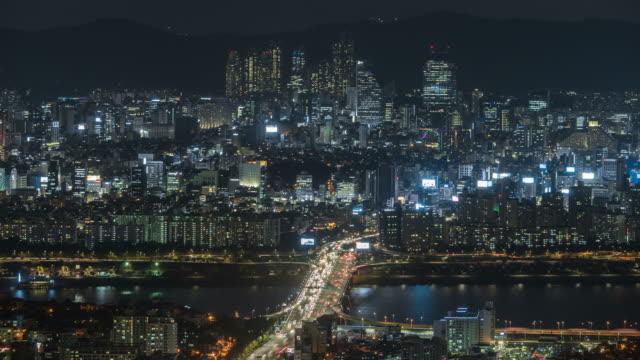 night scenery of traffic moving on the hannam bridge and skyscraper at the gangnam-gu - 乗り物の明かり点の映像素材/bロール