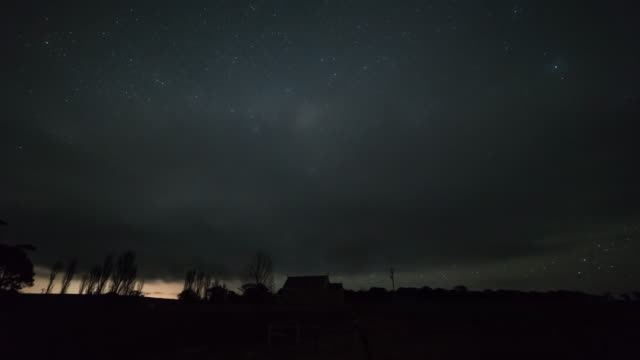 night scenery view of milky way and cloudscape over green fields - atmosphere filter stock videos and b-roll footage