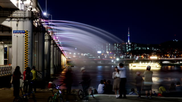 night scenery view of people enjoying moonlight rainbow fountain (famous tourist destination) and n seoul tower (famous tourist destination) - fotografische themen stock-videos und b-roll-filmmaterial