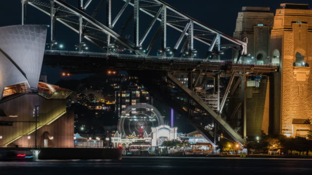 night scenery view of sydney harbor bridge (famous travel destinations) and luna park (amusement park) in distant - ニューサウスウェールズ州点の映像素材/bロール