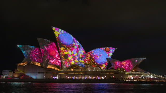 vídeos de stock, filmes e b-roll de night scenery view of visual lighting show on the roof of sydney opera house - sydney australia